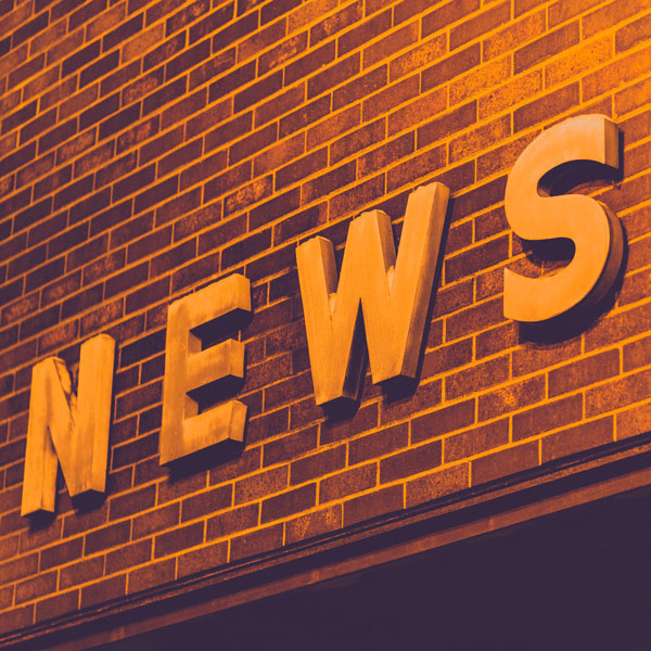 """The word """"news"""" on a brick wall"""